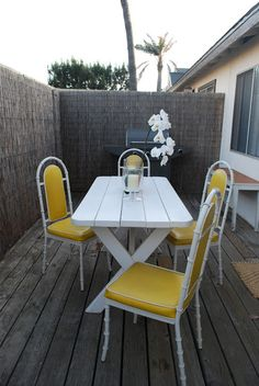 the perfect yellow thrifted outdoor chairs on The Gray Bungalow THIS LOOKS LIKE OUR DECK! DO THEY HAVE A BUSY STREET BEHIND THEM?