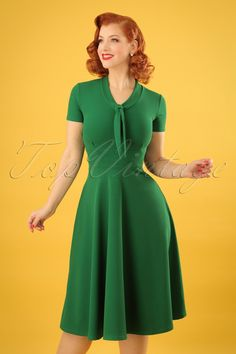 Feminine and flirty this 50s Lillie Swing Dress in Emerald Green!Wow, what a stunner! This vintage inspired beauty features an elegant V-neckline with a tie neck and flattering short sleeves. The combination of the semi-swing skirt with the fitted top creates a super feminine fifties silhouette. Made of a supple, stretchy crêpe-like fabric in emerald green that wears beautifully. This dress is sure to win your heart and not just yours... ;-)Semi-swing styleV-necklineTie neckShort…