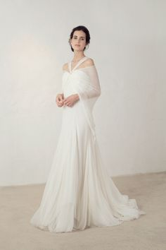 Cortana Wedding Dress. Jardin dress, a strapless silk bambula dress lined in silk stretch satin. It is fitted and has various draped pieces. Two straps go from the center of the neckline to the back and a piece of bambula falls from the back and can be used as a short cape to cover the shoulders. This design has organdy godets and it closes at the back with buttons lined in the same fabric. Made in Barcelona. Cortana Bridal Collection 2017. Shop now.