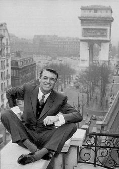 The irrepressible Cary Grant, Paris, 1956. Studio execs must have had apoplexy over this shot--valuable superstars weren't supposed to sit on the edge like this.  :D