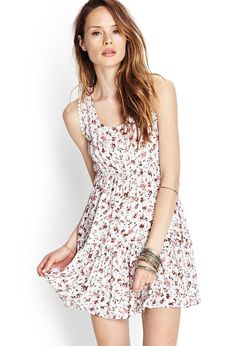 Flowy and lightweight, this tiered smock dress features a vibrant floral print and crochet trim. ...