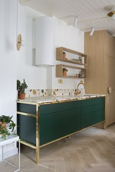 Bespoke kitchen design by Play Associates with brass frame, Max Lamb Marmoreal worktop, rose gold tap and sink, Atelier Areti lights and reclaimed parquet flooring