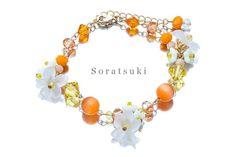 元気の出るオレンジカラーに透明感のあるサワハコベのお花と小さな白いお花を紡いだ、花の女神フローラのブレスレットです*素材:キャッツアイ、スワロフスキー、ドイツ...|ハンドメイド、手作り、手仕事品の通販・販売・購入ならCreema。