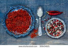 Spices over wood. Saffron, grey salt and peppercorn mix on dark wooden background. Cooking concept.