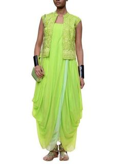This especial neon gown by Anita Dongre on strandofsilk.com is sure to steal the limelight. Inspired by the dhoti, the beautiful gown showcases an artfully inspired draped design. Teamed with a stunningly embroidered bandi, this enriched fusion look in a refreshing colour palette pairs perfectly with silver kholapuris and accessories for that exotic themed wedding reception #anitadongre #gown #dhoti #drape #neongreen #limelight #exotic #wedding #themewedding