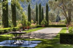 Gravel bocce ball court surrounded by a beautiful garden of bushes, flowers and trees with an iron dining table on a stone patio at the end.