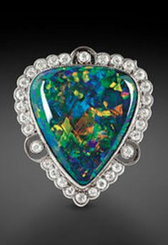 Art Deco Lightning Ridge Opal Brooch, A stunning black opal weighing 9.00 carats is showcase in this incredible brooch The rare stone hails from Australia's famed Lightning Ridge Mine The boldness of the stone is accented by 1.00 total carats of shimmering diamonds.  http://www.rauantiques.com/item/art-deco-lightning-ridge-opal-brooch.30-2352.html