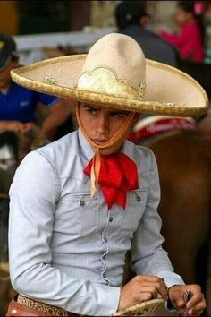 Mexican man showing his culture wearing q tight button down shirt, red handkerchief and a sombrero