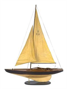 """This wood and fabric model sailboat is handcrafted with exacting detail. The dimensions are 39-1/4"""" x 8-1/2"""" x 53""""."""