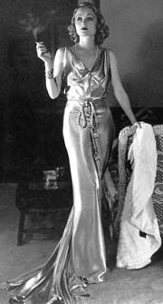 Carole Lombard, 1934 in slinky, metallic look v-neck gown with cord belt. According to http://fashionbloglife.com/1930sfashion/?doing_wp_cron - the evening wear of the 1930s had a glamour that was 'romantic, mysterious and spellbinding'.