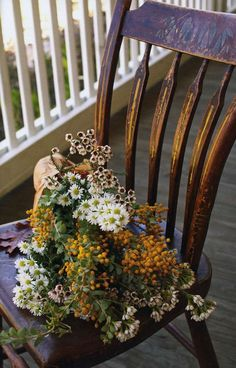 Distressed antique chair with a bouquet of flowers - perfect decoration for a front porch.