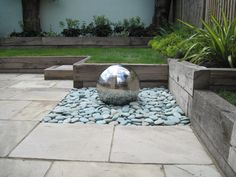 Just love these Stainless steel water features .something similar but on a bed of white cobblestones