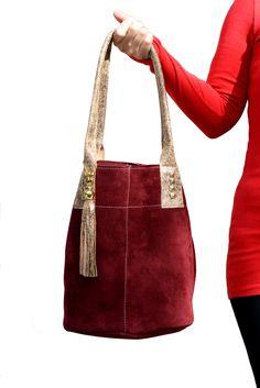 Bolso en gamuza bordó con manijas y fleco en cuero natural dorado. $560