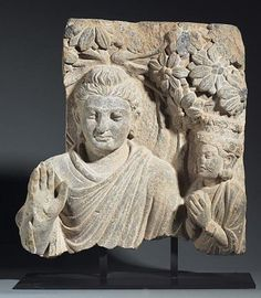 Gandhara, Hadda style, 4-5th century, NW Pakistan or Afghanistan.  A grey schist relief with a bust of the Buddha standing beneath a Bodhi tree with his right hand raised in abhayamudra (the gesture of dispelling fear)