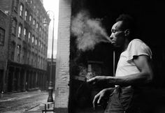 Man smoking in the streets under the Brooklyn Bridge. New York, 1955.  Joining Magnum in 1952, Erich Hartmann shared the Eastern European heritage of many of the agency's early photographers, having moved to New York in 1938 as a refugee. This image is taken from a series of street photographs that portray the more marginal and gritty parts of the city around the Brooklyn and George Washington bridges.