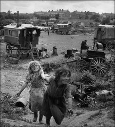 1951: Romani children- The Romani are believed to have originated in India,   and to have gradually migrated to the Near East   and Western Europe, reaching Scotland in the early   sixteenth century. They generally travelled in family groups,   and were associated with professions such as   hawking and peddling, acting as tinkers and street   performers, and most common of all, as fortune-tellers.