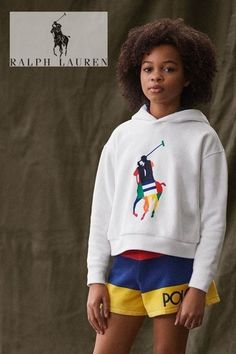 Cool White Big Pony Polo Ralph Lauren Hoodie Sweatshirt. Fall Streetwear look for Girls. Looks perfect with a pair of colorful striped shorts and a pair of white and blue sneakers. Complete the look with a colorful Polo logo beach bucket hat. Shop designer girls clothes @ Childrensalon (affiliate). #polo #ralphlauren #girlshoodie #girlstreetwear #childrensalon #dashinfashion Polo Ralph Lauren Hoodie, Polo Ralph Lauren Kids, Girls Designer Clothes, Beach Bucket, Girls Special Occasion Dresses, Polo Logo, Hat Shop, Blue Sneakers, White Hoodie