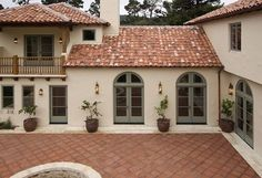 Exterior of a SPANISH STYLE LUXURY HOME with stucco walls a red tile roof and MEXICAN TILE PATIO : Stock Photo