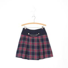 Sweet vintage plaid mini skirt circa the early 1970s. Navy blue high waisted panel with metal chain and button details. Plaid tartan skirt