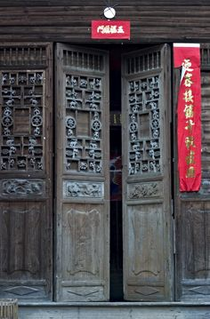 Chinese Door - the red signs above and beside the doors are New Year's Spring couplets, or poems. They're posted above and on both sides of the door and left exposed to the weather for the whole year for good luck. Feng Shui mirror above the door deflects bad spirits.