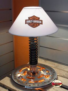"""Faak Brake"" incorporates a shock from an American motorcycle and uses a brake disk as a base. Just recently, for a client who owns a Harley and is passionate about his hobby, we upgraded our shade with a logo of his favorite brand. We added some LED lighting tech to turn this lamp into an exceptional design object on a table or desk in any environment. All our designs come with a lifetime warranty and we ship world wide."