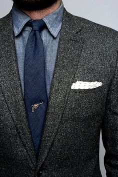 Grey coat, blue skinny tie, denim dress shirt, revolver tie tack