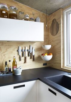 A mix of concrete, plywood and simple white kitchen elements, creates a  raw and urban kitchen.