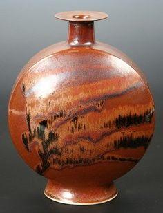 """VASE - Footed flask form vase with raised neck and wide flared rim by  Brother Thomas Bezanson (VT/PA, 1929-2007). Brown glaze with flowing black glaze, inscribed on bottom Benedictine Monks, Weston Vermont. From a collection purchased directly from Brother Thomas. 9"""" high, 7"""" wide, 4"""" deep, very good condition."""