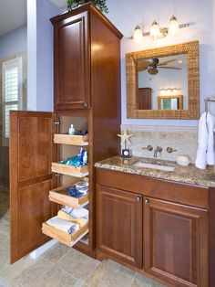 In this coastal-inspired bathroom with granite countertops and tile floors, a tall cabinet offers plenty of storage for toiletries and hair styling tools. Pull-out shelves make it easy to locate items stored toward the back.