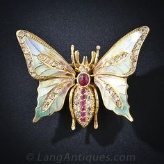 This enchanting butterfly pin, although not as old as its Art Nouveau predecessors on which it is modeled, is beautifully crafted using the same materials and procedures as those from the turn of the century. The en tremblant wings (they vibrate on a spring) are composed of translucent Plique-a-Jour pastel color enamel and enhanced by glittering rose-cut diamonds. Her abdomen is composed of bright red rubies and rose-cut diamonds.