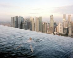 The swimming pool on the 57th floor at the Marina Bay Sands Hotel, Singapore; Singapore's financial quarter is in the background. From The Heavens, Annual Report by Paolo Woods and Gabriele Galimberti