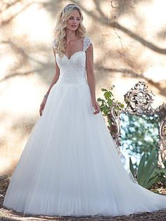 Maggie Sottero - MINDI, Dreamy lace and tulle combine to create this romantic ball gown wedding dress with fitted lace bodice sparkling with Swarovski crystals, and a billowing tulle skirt. Finished with sweetheart neckline and covered buttons over zipper and inner corset closure. Detachable beaded lace cap-sleeves sold separately.