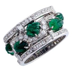 Carved Emerald Diamond Ring USA 1930s Designed as an undulating foliate line of brilliant-cut diamonds accented at regular intervals with carved emeralds, between two bands of single-cut diamonds embellished with baguette stones, circa 1930, Ring size 6.