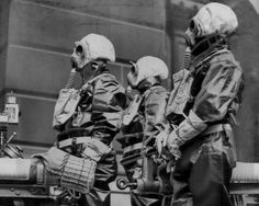 England's largest demonstration of its readiness against chemical warfare was staged on March 16, 1938, when over 2000 volunteers in Birmingham donned gas marks and went through an elaborate attack drill. These three photographed here were firemen, fully equipped from their rubber boots to masks.
