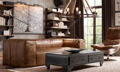 So very industrial, the timber shelving, leather furniture, metal coffee table and exposed bulb/rope pendant. Via Rooms   RH