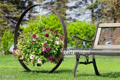 Stock Photo : Flower Basket Hanging on Wagon Wheel by Garden Bench