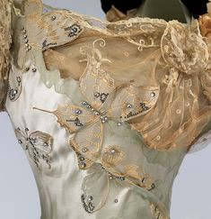 This gown is made from a very special fabric which was woven à la disposition to fit the shape and dimensions of the skirt so that the butterflies flutter upward from the hem and, being graduated in size, seem to disappear in the distance