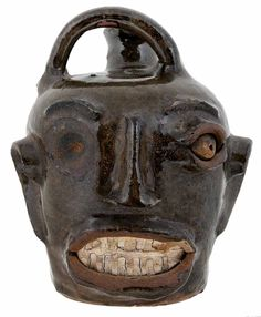 Rare Edgefield Stoneware Face Harvest Jug (Edgefield District, South Carolina, 1860s), light olive green alkaline glaze with brown mottling, loss to right eye structure during firing, 6 in. Private Collection, Atlanta, Georgia. Brunk, 01/28/2017, $30,000 + prem.