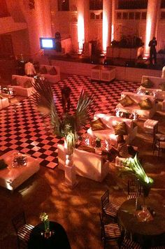 a black and white checkered dance floor is bathed in red light. Click to learn more about using custom flooring at your wedding.