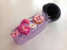Heavy duty purple glass pipe with black bowl. Decorated with Alice in Wonderland themed charms and matching rhinestones!Approximately 5 inches.