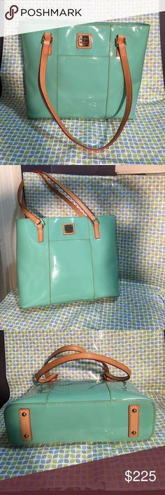 """Dooney & Bourke Handbag NWT Gorgeous seafoam patent leather in color with butterscotch shoulder straps contrasting with red trim. Interior zipper pocket and an additional pocket just below zipper pocket. On the opposite side there are 2 divider slots that button down your items for safe keeping. Exterior Slide pockets in front and back of Handbag. Classic DB Handbag is a fun color and is currently sold out in this style and color. New, In pristine condition, flawless. Measures 11.5""""L X 10""""H…"""