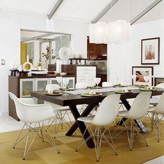 Modern city style    In this condominium dining room, bases on contemporary molded-plastic chairs subtly repeat the X-base wood table. A stark white-and-brown color scheme has a definite city/urban feel. The pass-through to the kitchen, with a serving buffet underneath, offers flexibility for entertaining.