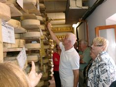 Latteria Perenzin cheese maker Carlo Piccoli explains the cheese aging process e Sarasota Sister Cities member Peggy Abt during the groups visit to Treviso Province in 2010