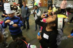 Soheni Dutta, 6, of Buffalo Grove, right, blows bubbles with other children during the New Year's Noon Celebration on Monday at the Vernon Area Public Library in Lincolnshire. About 40 children joined their parents making hats and noise makers, singing songs and dancing until the countdown began for the new year.