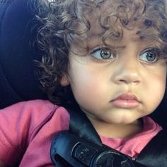 Handsome little boy with bright eyes and curly hair