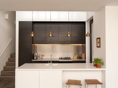 Modern kitchen with a series of brass pendants - Decoist