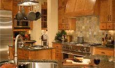 Kitchen with a stone tile backsplash and a pot rack above the island.