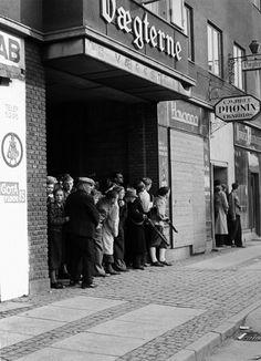 Members of the Danish Resistanceand civilians take cover from German snipers in doorways on a street in Aalborg. Aalborg, North Jutland,Denmark. May 1945.