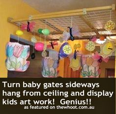 Use baby gate on ceiling to hang art work