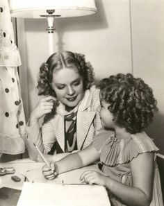 "Alice Faye helping Shirley Temple finish her homework on the set of ""Stowaway"", 1936"